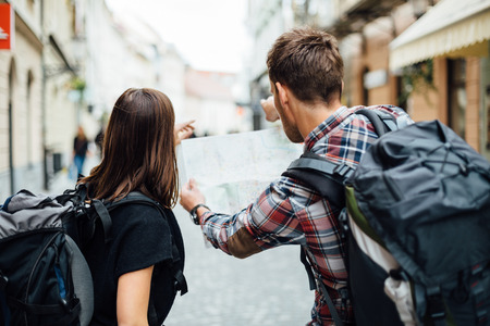 Couple of backpackers looking at city map  Stock Photo