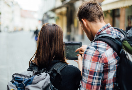 Couple of backpackers looking at city map on tablet computer Stock Photo - 27639834