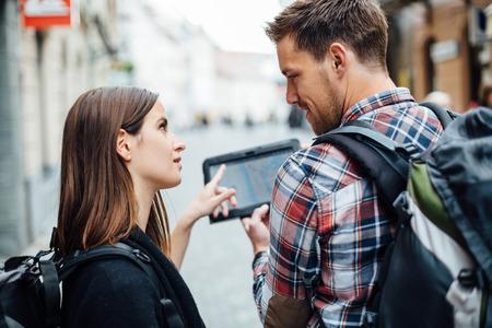 Pár batohem na zádech při pohledu na mapu města na tablet počítač Reklamní fotografie