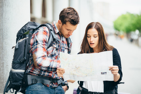 lost city: Backpackers looking at city map on street Stock Photo