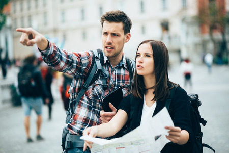backpackers: Tourists looking for landmarks in city using map Stock Photo