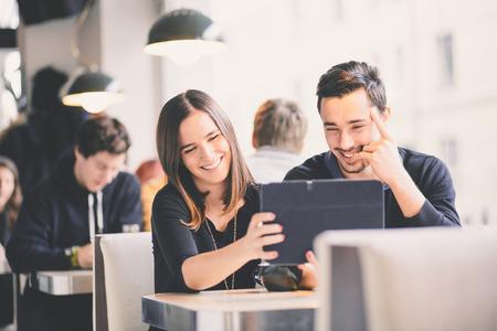 タブレット コンピューター笑って写真を探しているカップル