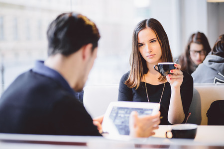 novios enojados: Mujer joven enojada con su novio novio para con tablet PC en el café