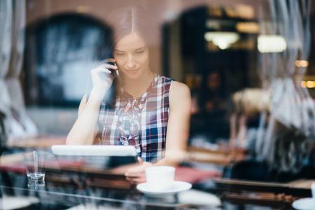 internet cafe: Mujer joven hablando por tel�fono y usando la computadora de la tableta en la cafeter�a