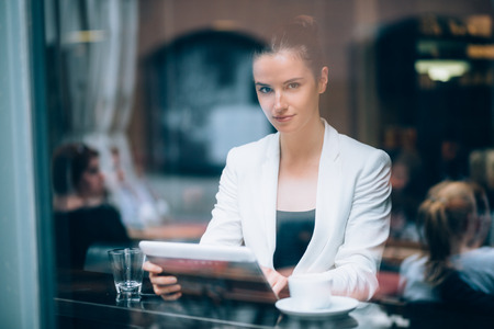Beautiful young businesswoman using tablet computer in coffee shop photo