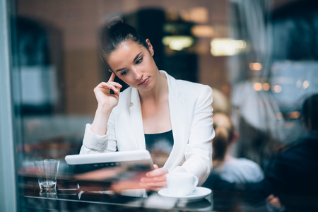 Pensive young businesswoman using tablet computer in cafe photo