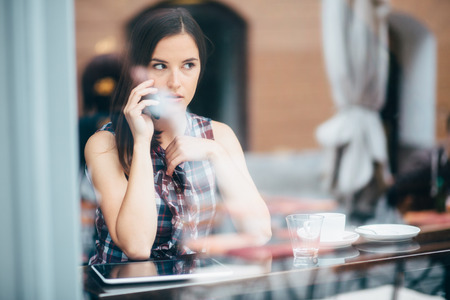 Young woman talking on phone in coffee shop photo