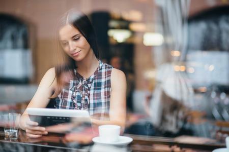cafe internet: Mujer joven con tablet PC en la cafetería