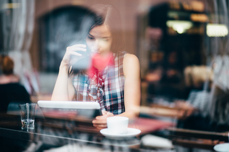 shop window: Young woman talking on phone and using tablet computer in coffee shop Stock Photo