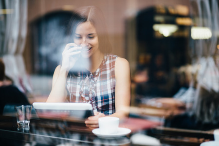 Young woman talking on phone and using tablet computer in coffee shop photo