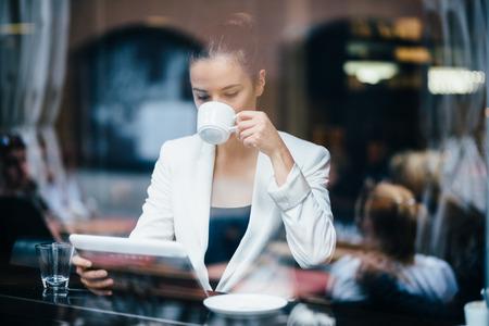 cafe internet: Joven empresaria de tomar café y el uso de Tablet PC en el café