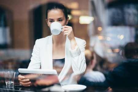 Pensive young businesswoman drinking coffe in cafe photo