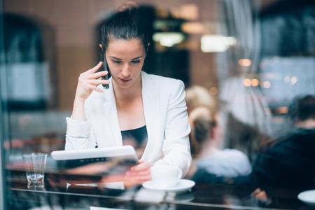 cafe internet: Joven empresaria hablando por teléfono en la cafetería Foto de archivo