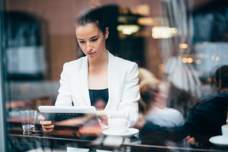 Young businesswoman using tablet computer in coffee shop Banco de Imagens