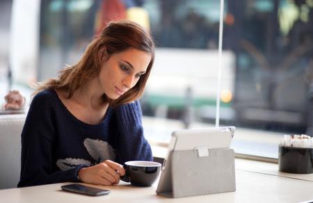 紅茶コーヒーを飲みながらタブレット コンピューターを使用する若い女性の率直なイメージ