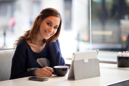 Gelukkige jonge vrouw met behulp van tablet-computer in een cafe