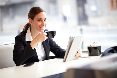 Businesswoman on a coffee break, using tablet computer photo