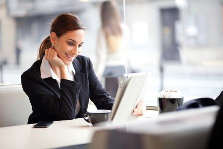 セレクティブ フォーカスのカフェでタブレット コンピューターを使用して幸せな若い busineswoman