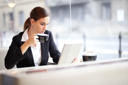 woman drinking coffee: Businesswoman having a cup of coffee while reading an article on her tablet computer  In a cafe  Stock Photo
