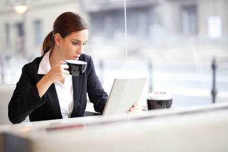 Zakenvrouw met een kopje koffie tijdens het lezen van een artikel op haar tablet-computer in een cafe