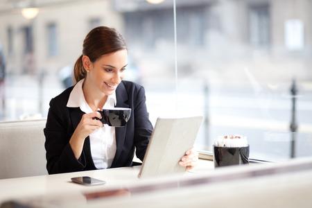 カフェでの彼女のタブレット コンピューターについての記事を読んでいる間コーヒーのカップを持つ実業家