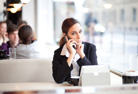 Worried businesswoman talking on the phone in a cafe photo