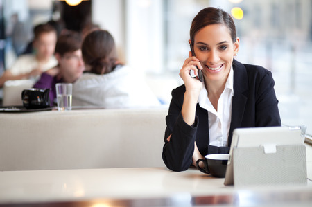Cheerful businesswoman on a coffee break talking on the phone in a cafe photo