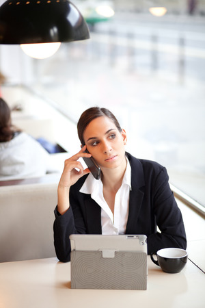 Businesswoman talking on the phone in a coffee shop photo