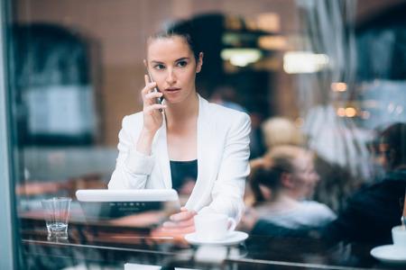 mujer pensativa: La empresaria joven hablando por teléfono en la cafetería Foto de archivo