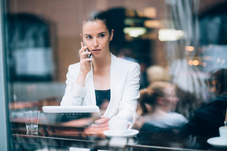 Young businesswoman talking on the phone in coffee shop photo