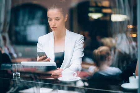 Young Businesswoman using smartphone and tablet computer in coffee shop photo