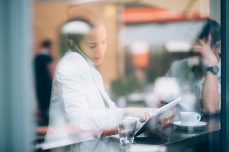 tazas de cafe: Empresaria ocupada hablando por tel�fono y con tablet PC en la cafeter�a Foto de archivo