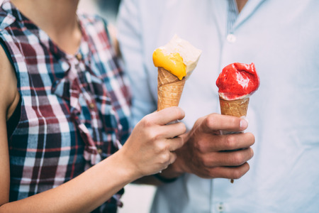 woman with ice cream: Couple eating ice cream on street Stock Photo