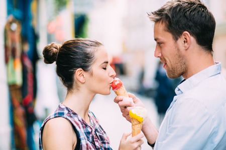 Young man feeding ice cream to girlfriend