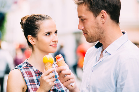 Couple eating ice cream on street Фото со стока