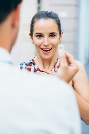 proposed: Surprised young woman getting proposed by boyfriend
