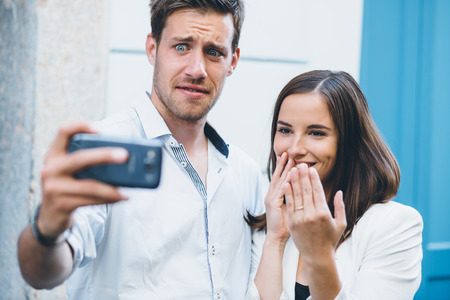 Young couple taking a selfie after engagement  Man is having second thoughts  photo