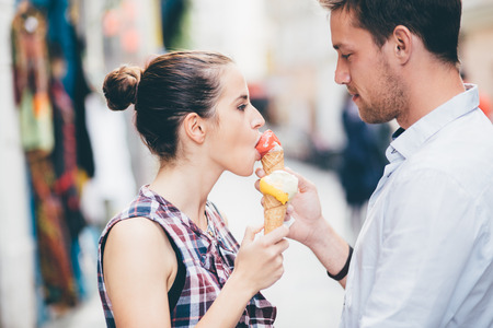 sweet smile: Young man feeding girlfriend ice cream