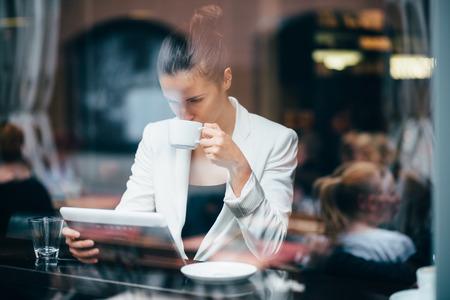コーヒーを飲みながらカフェでタブレット コンピューターを使用して若い実業家