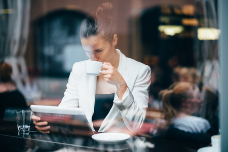 Young businesswoman drinking coffee and using tablet computer in cafe Stock Photo