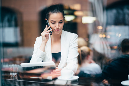businesswoman suit: Young businesswoman talking on the phone in coffee shop