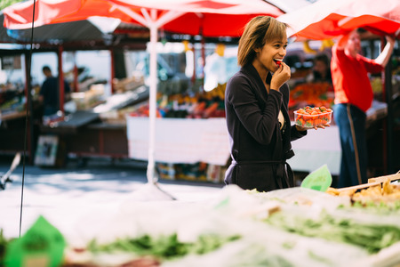 Young woman buying strawberries at farmers market photo