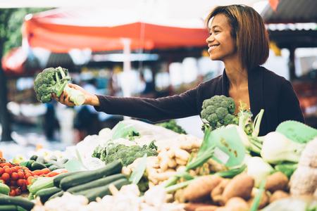 campesino: Mujer joven comprar verduras en el mercado de los agricultores