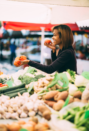 Young black woman buying vegetables at farmers market photo