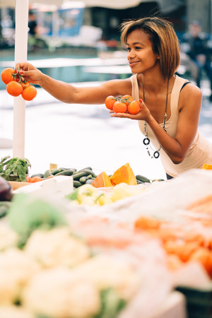 Young woman buying vegetables at farmers market photo