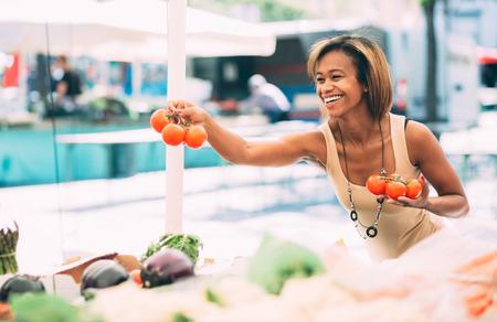 Jonge zwarte vrouw het kopen van groenten op boerenmarkt Stockfoto