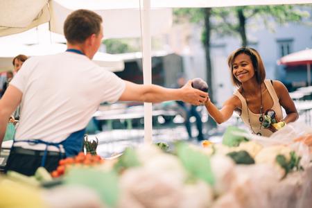 若い女性の農民市場で野菜を買う
