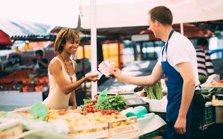 Jonge vrouw betalen voor producten die bij de boeren markt