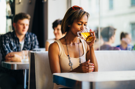 Young woman drinking beer in a bar photo