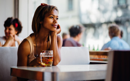 Young pensive woman drinking beer in a bar Stock Photo - 28471664